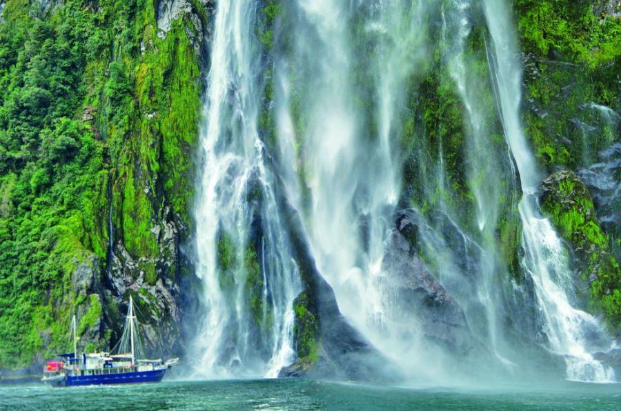 El parque nacional de Fiordland abarca un rincón montañoso de la isla Sur de Nueva Zelanda. Sierras, valles glaciares, lagos y fiordos componen su paisaje en buena parte virgen. Se puede recorrer a través de tres grandes senderos señalizados, navegar sus ríos en kayak y dormir en cabañas típicas. En la foto, un barco turístico en Milford Sound.