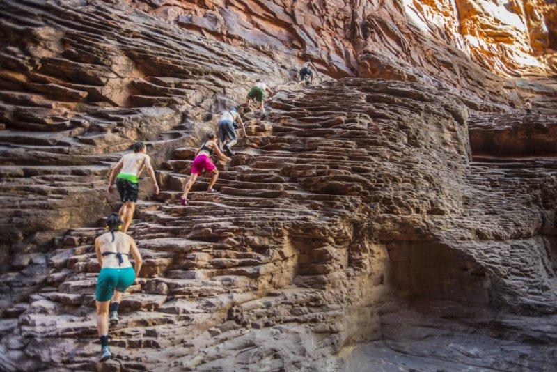 Cuatro millones y medio de personas visitan cada año el parque nacional del Gran Cañón, en Arizona, Estados Unidos. Los visitantes pueden asomarse al vacío desde la vertical de 1.300 metros del Skywalk, una pasarela de acero con suelo de cristal, o adentrarse en sus entrañas como los jóvenes de la foto, tomada en el North Canyon, una garganta con espectaculares escalones de arenisca. Este enclave forma parte de las rutas senderistas de las empresas de turismo activo de Salt Lake City, Phoenix o Flagstaff. La mayoría de los turistas que acceden por carretera lo hacen por la cornisa sur (South Rim), desde las ciudades de Williams o Flagstaff hasta Grand Canyon Village, la zona de servicios dentro del parque nacional. El Gran Cañón mide 446 kilómetros de este a oeste y ocupa 5.000 kilómetros cuadrados. En sus paredes se han identificado 40 estratos de rocas diferentes —las más antiguas, de 1.800 millones de años—, un registro que abarca tres de las cuatro eras geológicas de la Tierra.