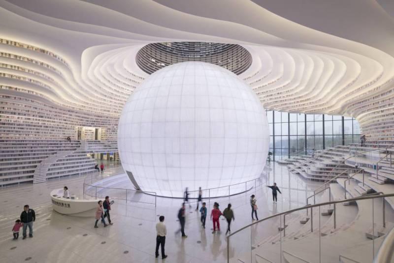 En la nueva área de Binhai, en la costa de la municipalidad de Tianjin (China), se acaba de inaugurar una impactante biblioteca pública de cinco pisos obra del equipo de arquitectos holandés MVRDV. Concebida como un gran ojo que se admira desde el exterior a través de una gran cristalera, en el interior una enorme bola luminosa (que encierra un auditorio) representa a un omnisciente globo ocular. En las estanterías que lo circundan, los libros se acumulan en superficies continuas y alabeadas. Los usuarios se sientan a leer y el luminoso espacio se transforma así en una cueva de la inteligencia y el saber donde los conocimientos se absorben a través del ojo humano. La biblioteca se completó muy rápidamente, en apenas tres años desde el encargo. Por encima de las estanterías al alcance de la mano, otros libros dibujados sobre paneles crean en las zonas superiores una ilusión óptica, un trampantojo espacial. La biblioteca forma parte de un complejo que incluye un recinto ferial proyectado por el equipo alemán GMP.