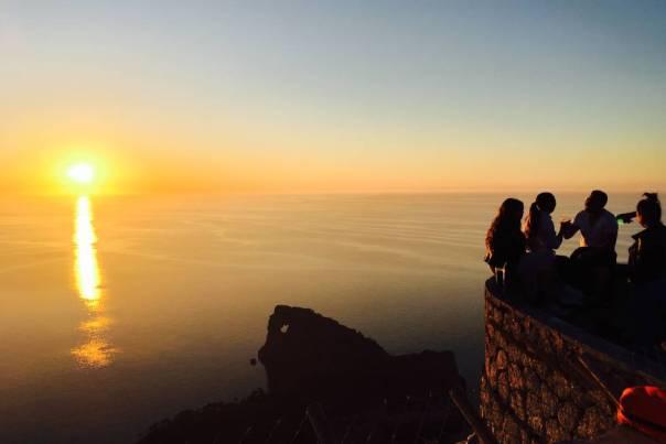 La puesta de sol congrega a viajeros y turistas en el Mirador Sa Foradada, entre la cala de Deià y el caló de S'Estaca, en la costa oeste de Mallorca , inmerso en el paisaje espectacular de la Sierra de la Tramuntana y con vistas a un curioso (y conocido) accidente geográfico de la isla: una pequeña península que se adentra en el mar, con la roca agujereada (foradada) que le da nombre en su parte final, y que ha servido de inspiración a viajeros y artistas. Es un clásico asomarse a este balcón para hacerse un selfie o disfrutar de la postal desde la terraza del restaurante Na Foradada (naforadada.es) .