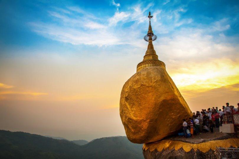 Um único fio de cabelo de Buda impede que essa pedra despenque da borda rochosa, ou assim diz a tradição. A Pedra Dourada, de 7 metros de altura, no topo do Monte Kyaiktiyo, no Estado de Mon, é um dos lugares mais sagrados de Mianmar, e os peregrinos budistas (apenas homens) foram cobrindo sua superfície com folhas de ouro e construíram uma estupa dourada (um santuário budista) no alto. A melhor época para a visita é de novembro a março, período de peregrinação, entre velas, oferendas de frutas e cantos dos monges. Os peregrinos tiram as sandálias para a subida de 11 quilômetros desde Kinpun. Os demais visitantes embarcam em caminhões que sobem a estrada quando estão com a lotação completa. A visita ao entardecer é espetacular, mas os caminhões param de circular no pôr do sol, então é melhor ficar em uma pousada perto do pagode. De Rangun se chega a Kinpun de ônibus em cerca de cinco horas.