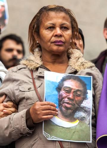 Aristides Santana, empregada doméstica, com a foto do filho assassinado