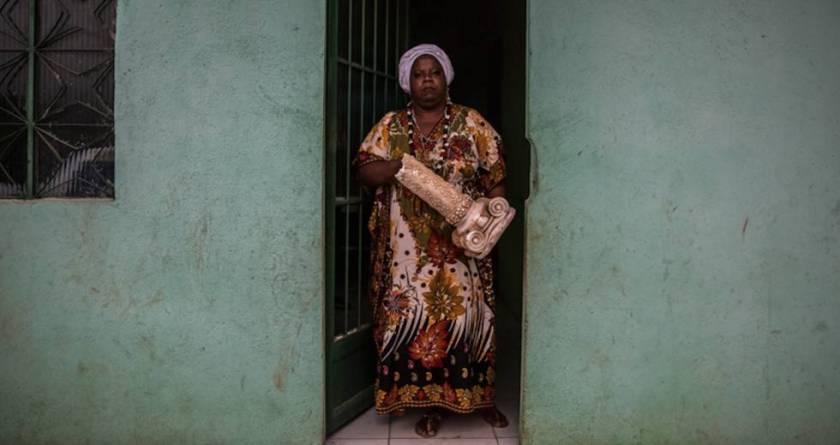 Mãe Vivian na porta da casa em Sepetiba com parte da estrutura da casa de Seropédica em mãos.