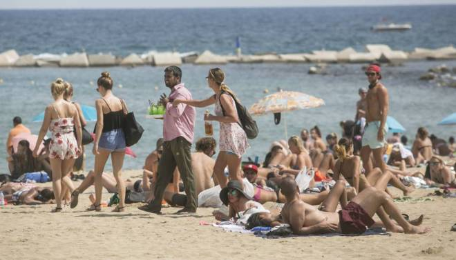 A plain clothes police officer stops a vendor on the Barceloneta beach on Wednesday.