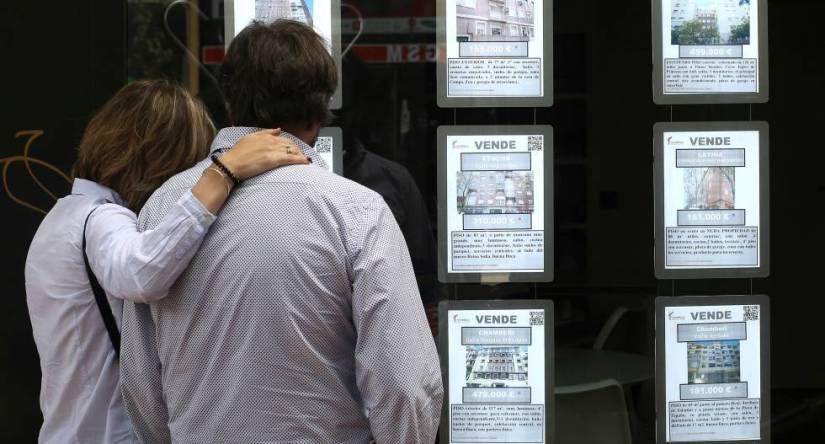 Una pareja observa anuncios de pisos en una inmobiliaria en Madrid