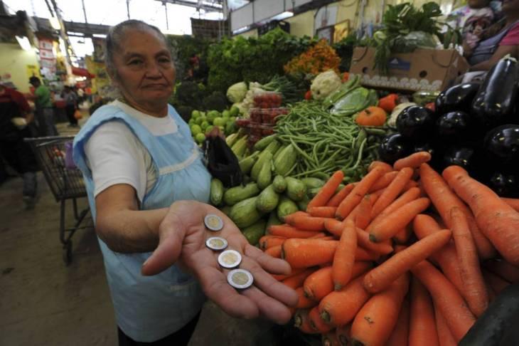 Una mujer cuenta su dinero en un mercado de la Ciudad de México.