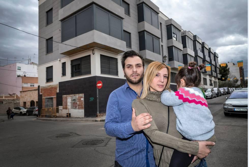 Luis Macía posa junto a su mujer y su hija frente a la urbanización de pisos inacabada en Benimamet.
