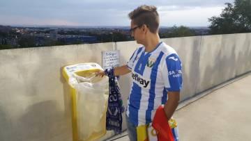 Un aficionado del CD Leganés deposita un vaso de plástico en la papelera.