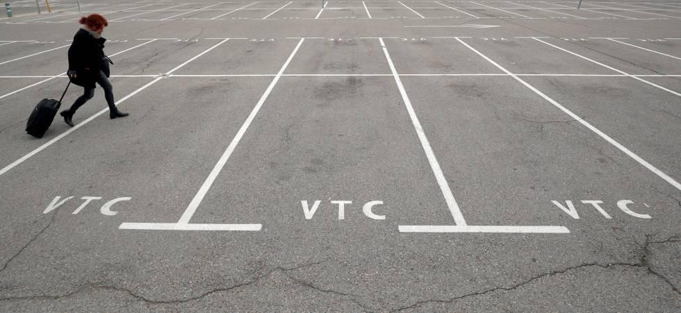 Una pasajera camina por el aparcamiento vacío de VTC en el aeropuerto de Barcelona.