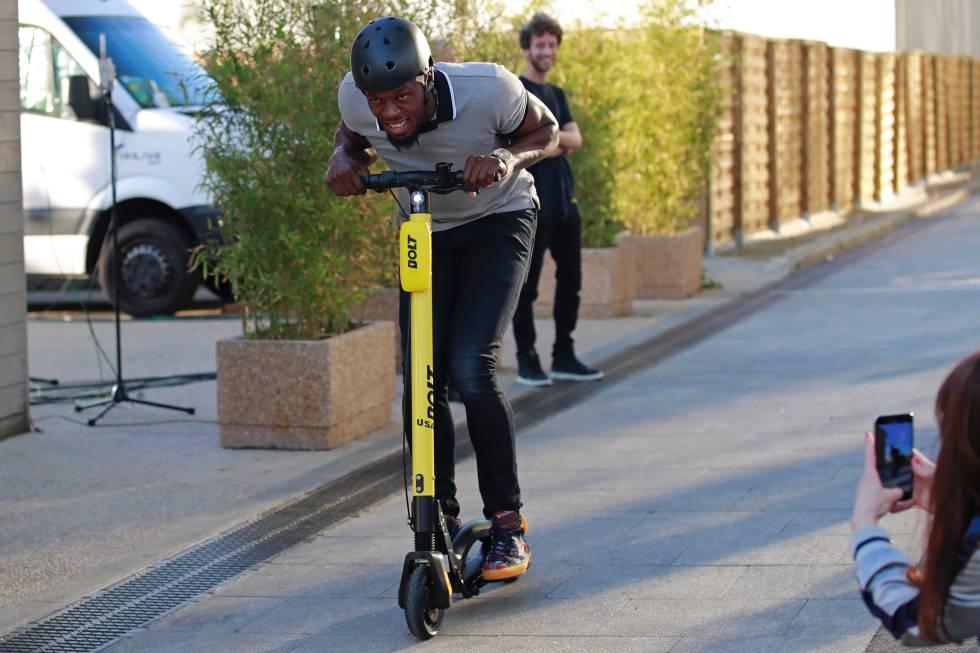 Usain Bolt montado en un patinete en París.