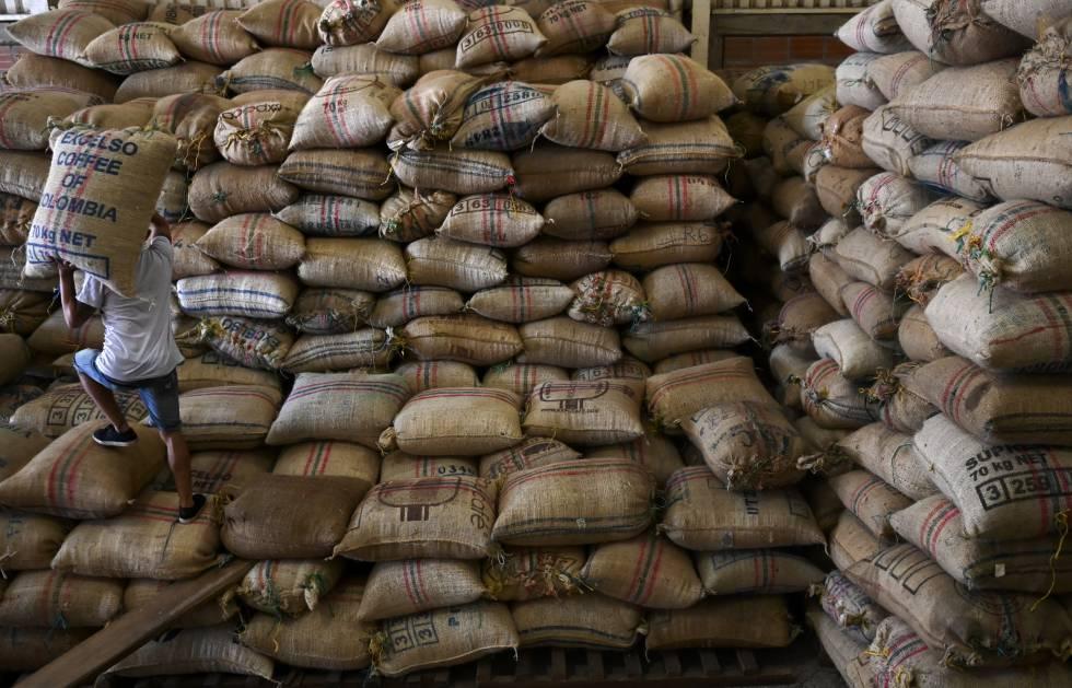Un hombre apila sacos de café en una cooperativa de Santuario, en Colombia.
