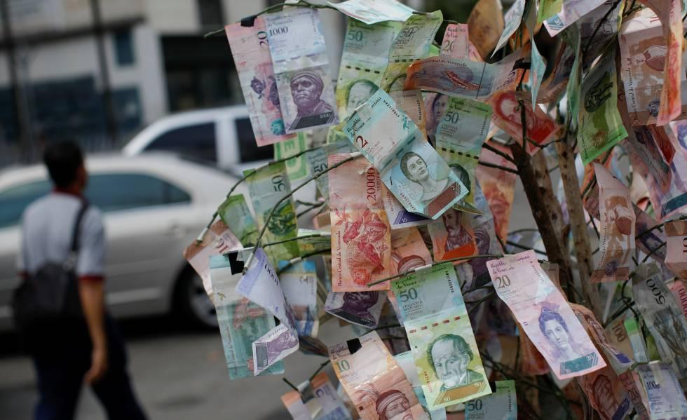 Un hombre pasa frente a billetes de bolívar tendidos en una calle de Caracas.