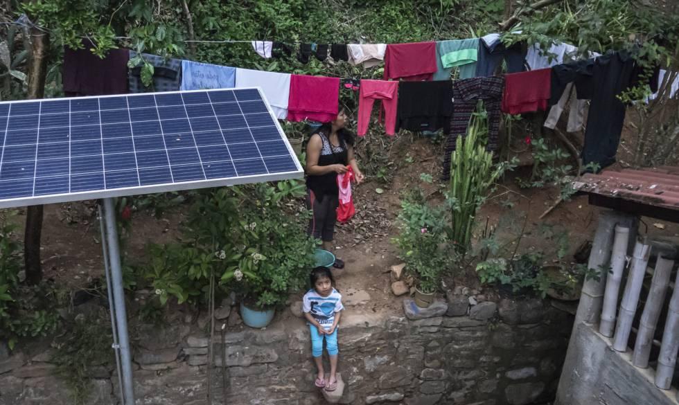 Una mujer tiende la ropa junto a un panel solar recién instalado en Zicuilapa.