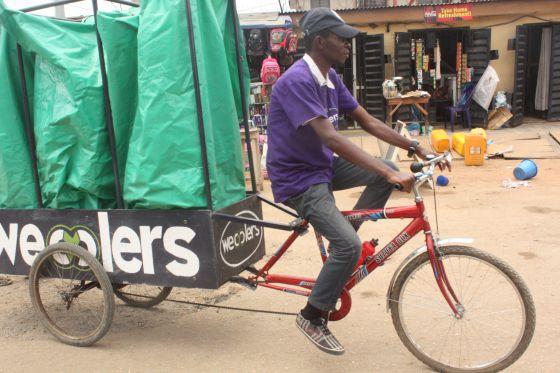 Un recolector de residuos con su bicicleta modificada en Lagos