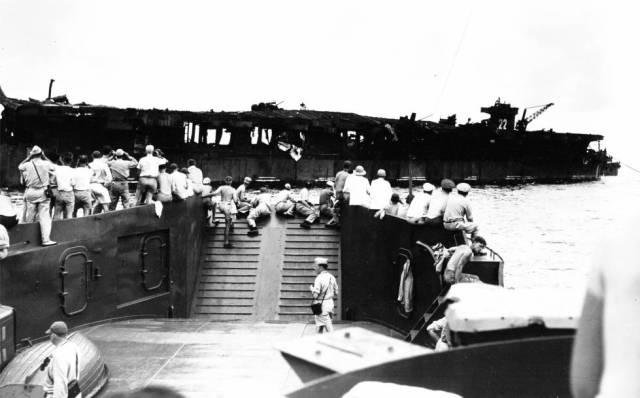 Militares observam o 'USS Independence' após a detonação de 1o. de julho de 1946.