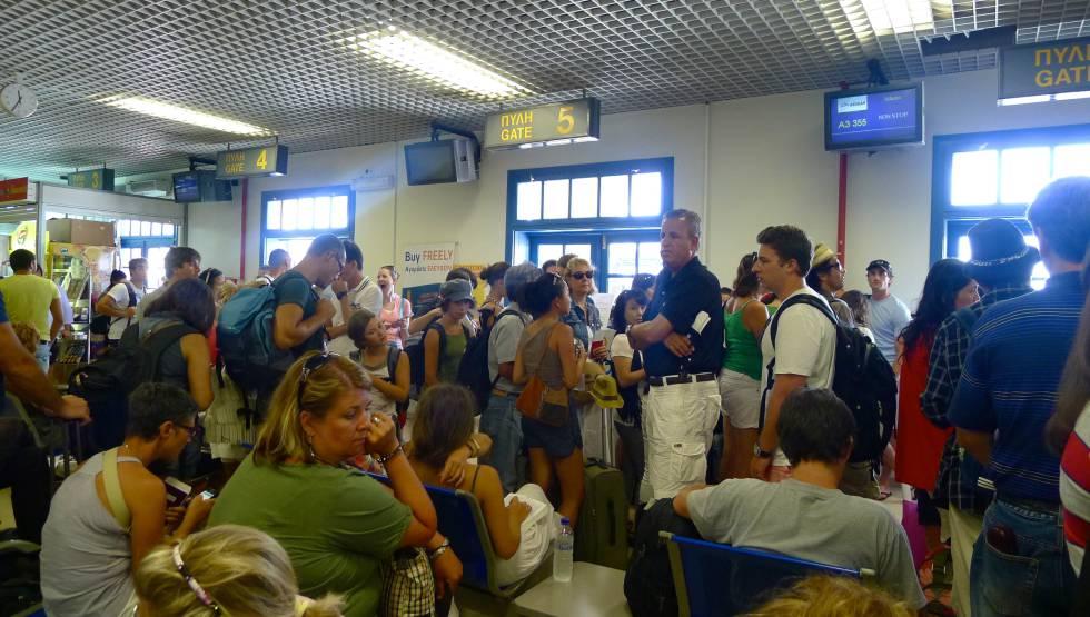 Passageiros esperando em frente às portas de embarque no aeroporto de Santorini.