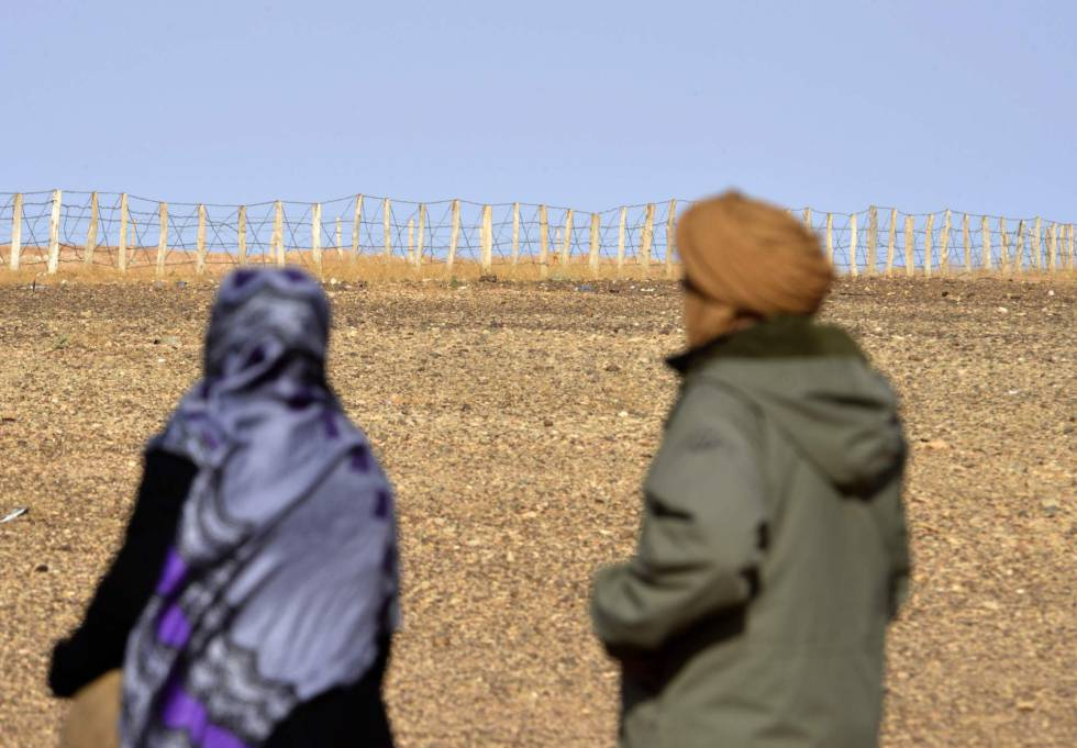 Dos personas contemplan la valla que separa las zonas controladas por Marruecos y el Frente Polisario en el Sáhara Occidental.