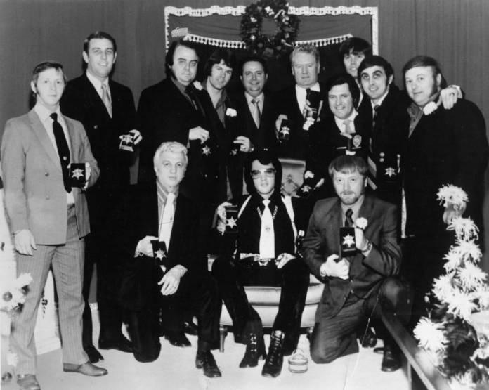Elvis Presley y su séquito -conocido como la Memphis Mafia- muestran las insignias que acaban de recibir del sheriff Nixon en Graceland, mansión del músico, en 1970. De izquierda a derecha en la fila de atrás, Billy Smith, el ex sheriff Bill Morris, Lamar Fike, Jerry Schilling, el sheriff Roy Nixon, Vernon Presley (padre de Elvis), Charlie Hodge, Sonny West, George Klein, Marty Lacker. En primera fila, de izquierda a derecha, el doctor George Nichopoulos (médico de confianza de Presley), Elvis y el actor Red West.