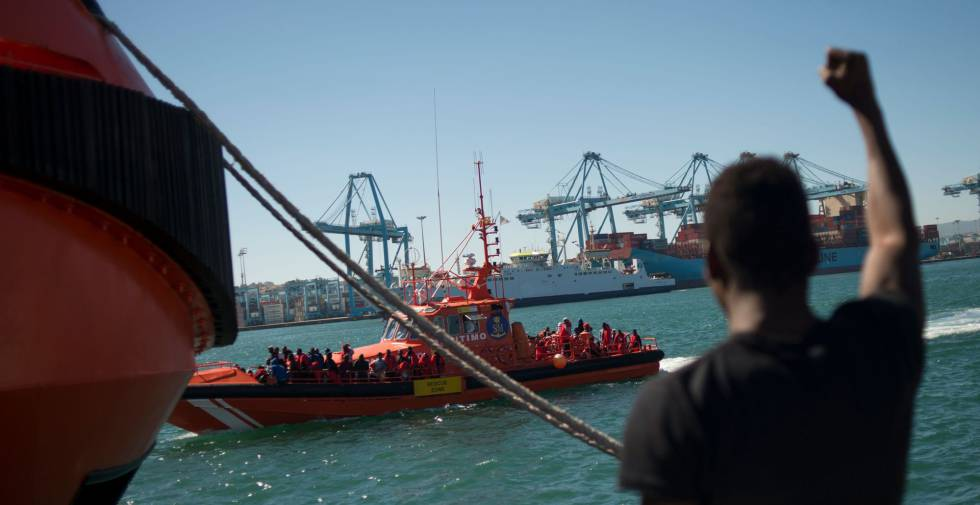 Un hombre saluda en el puerto de Algeciras a unos migrantes recatados en el mar.