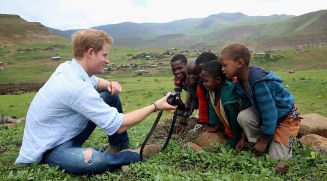 El príncipe Enrique de Inglaterra juega con unos niños y una cámara de fotos en una visita a una escuela construida en Mokhotlong, Lesotho gracias a su ONG Sentebale, el 8 de diciembre de 2014.