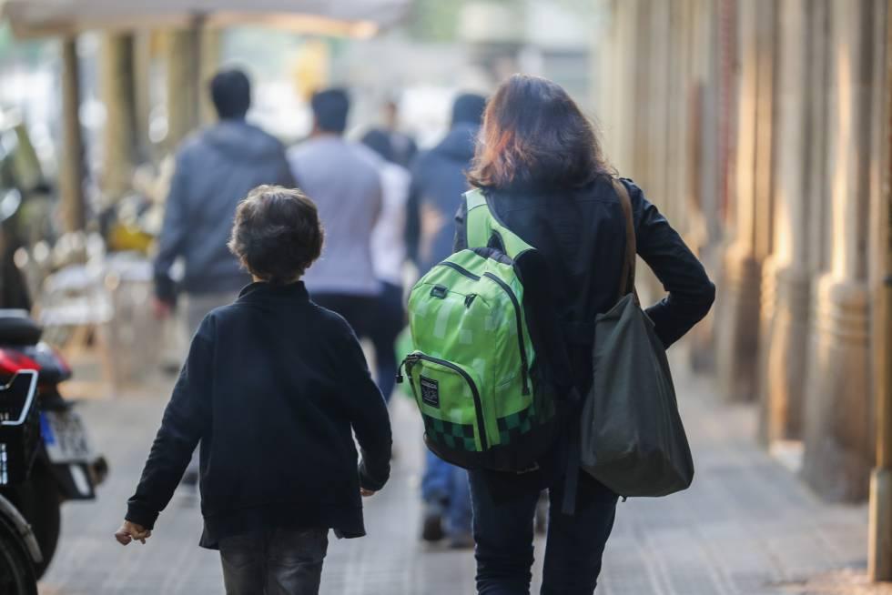 Una madre lleva la mochila de su hijo camino del colegio.