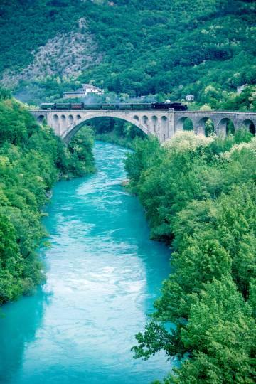 El antiguo tren a vapor de la línea de ferrocarril de Bohinj en un puente sobre río de Soca (Eslovenia).