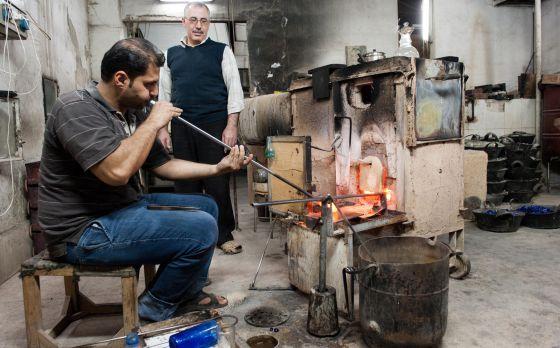 El soplador de vidrios Bachar Jalil trabajando junto a Mohamed el Jalak en la fábrica Beit el Azaz de Damasco.