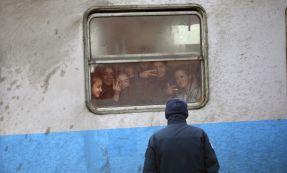 Un policía croata frente a un grupo de inmigrantes en un tren, este viernes cerca de la frontera con Serbia.