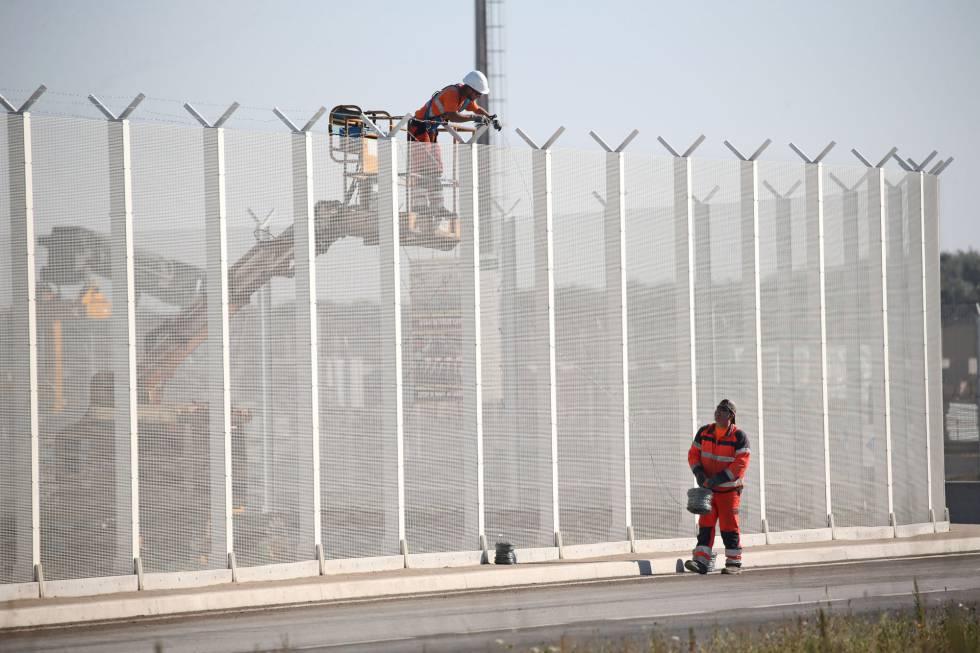 Operarios franceses colocan, este miércoles, alambres de púas en una valla del puerto de Calais