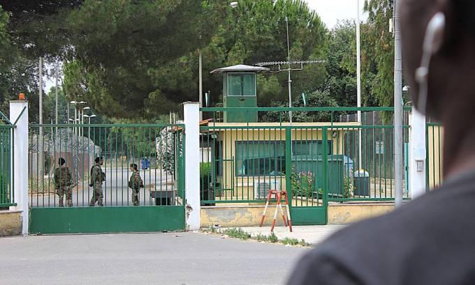 Un inmigrante, en la puerta del centro que estaba controlado por la mafia en Isola di Capo Rizzuto