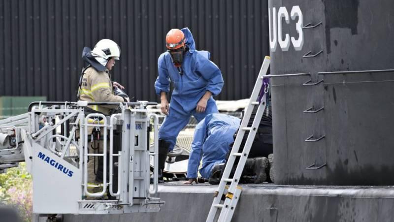 Policiais dinamarqueses no submarino depois de ser trazido à tona.