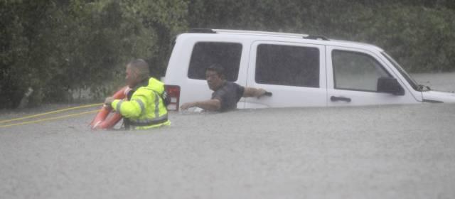 Un agente del sheriff rescata a un hombre de su coche en Houston, el domingo.