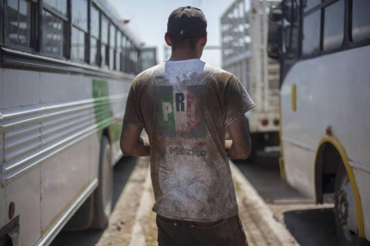 Un mecánico arregla un autobús en la carretera de San Pedro a Piedras Negras.