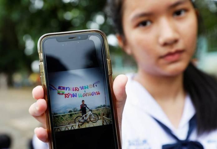 Estudante mostra uma foto de seu colega Prachak Sutham, um dos garotos presos na gruta de Tham Luang (Tailândia).