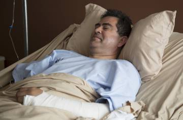 El padre Ezequiel Sánchez, herido en el accidente aéreo de Durango, en su cama en el Hospital del Parque antes de ser operado.