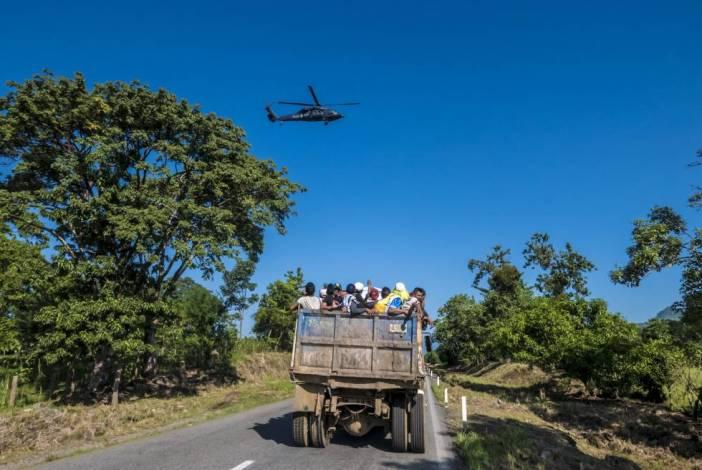 Un grupo de hondureños es llevado en un camión de materiales. Arriba, un helicóptero de la policía federal mexicana vigila su trayecto.