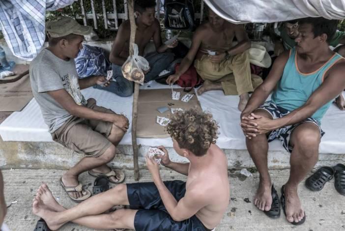 Un grupo de hondureños juega a las cartas mientras espera su próxima salida en Pijijiapan.