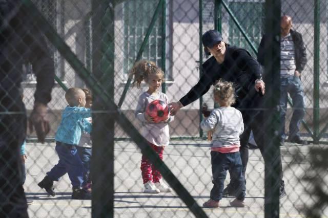 Una agente de policía juega con niños repatriados con sus madres desde Siria, el sábado en un centro de detención de Kosovo.