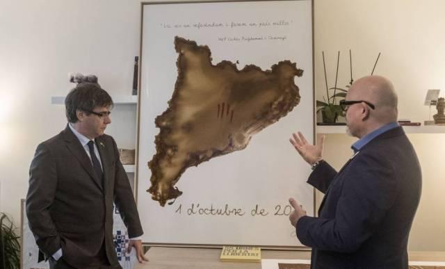 Puigdemont escucha la explicación sobre una de las obras que le han regalado, en Waterloo (Bélgica).
