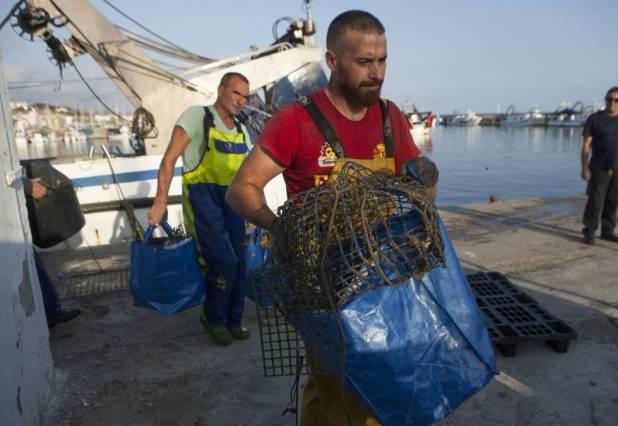 Dos marineros del Caleta Vélez descargan los plásticos hallados en caladeros para que personal de la Asociación Vertidos Cero lo segmente y gestione para su reciclaje.
