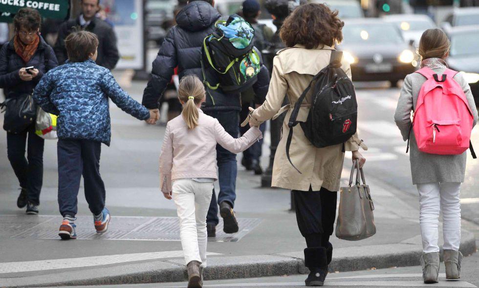 Una madre acompaña a sus hijos al colegio.
