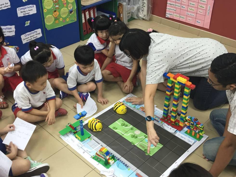 Crianças de quatro anos brincam com o BeeBot, abelha-robô usada no ensino de programação, em Cingapura.