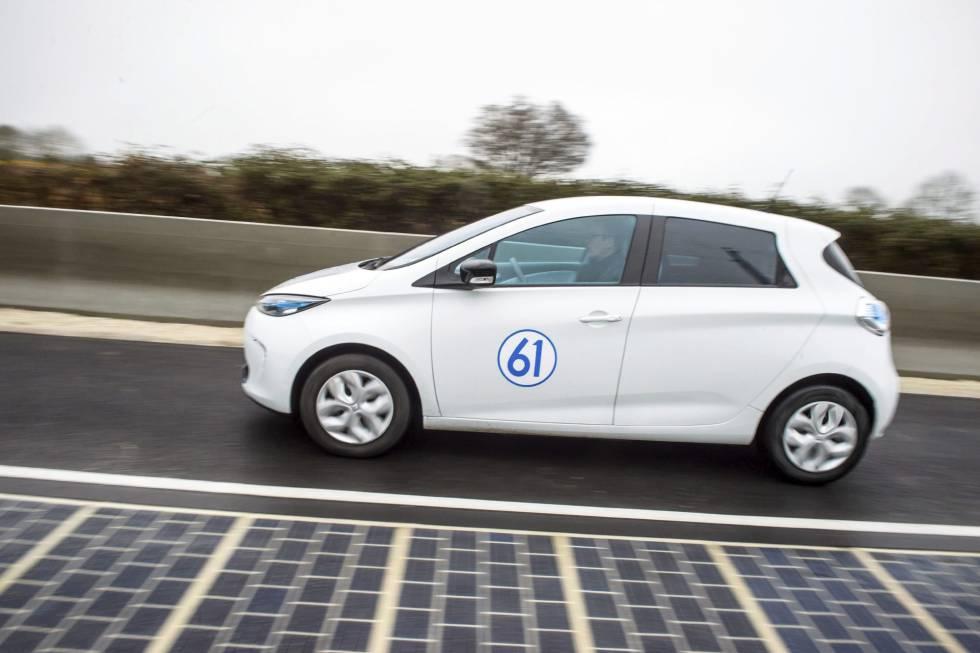 Un coche eléctrico conduce en la primera carretera equipada con paneles solares, en Tourouvre au Perche, Francia.