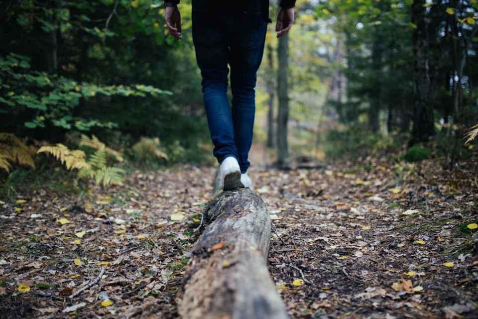 Une personne entrain de marcher en équilibre sur une branche.dépenser.