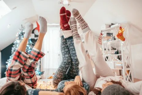 3 adults wearing pajamas with there legs up in the air