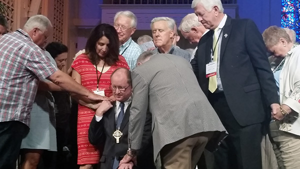Former Moderators in attendance at the 35th General Assembly lay hands on Mike Moses as the Assembly prays for the newly elected Moderator.