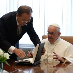 Pope Francis, right, finishes signing a guest book as United Nations Secretary Ban Ki-moon helps him close the book at the United Nations headquarters, Friday, Sept. 25, 2015. (Joshua Lott/Pool Photo via AP)
