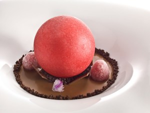 Iced sphere of red fruit on tea cream with crystallized raspberries