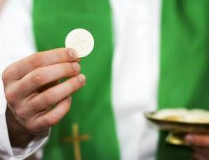 Image of priest holding a wafer and a chalice