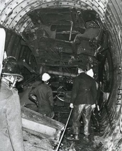 Moorgate crash. Crumpled wreckage of a Northern line car. The vehicle has been crushed against the roof of the tunnel which is of main-line height. Firefighters inspect the wreckage. Photographed by J A Ballard, 28 February 1975